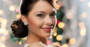 Frau mit Diamantohrring über Weihnachtslichtern Stockfotografie