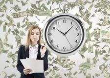 Frau mit Dokumenten in einem Raum mit einer Stoppuhr und Dollar Lizenzfreie Stockfotografie