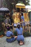 Frau mit drei Balinese vor kleinem Schrein für Gebet stockfotos