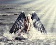 Frau mit dunklen Engelsflügeln Stockfotografie