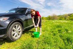 Frau mit Eimer-Auswringen-Schwamm nahe bei Auto Stockfotos