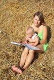 Frau mit einem Baby, das ein Buch auf einem Heuschober liest Lizenzfreies Stockbild