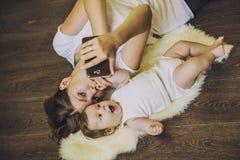 Frau mit einem Baby, das ein selfie liegt auf Boden tut Lizenzfreies Stockfoto