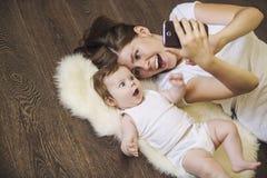 Frau mit einem Baby, das ein selfie liegt auf Boden tut Stockbild
