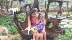 Frau mit einem Baby Papageien eingezogen Mamma- und Tochterlachen plappert Kindertagesstätte nach stock video