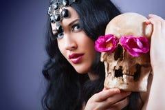 Frau mit einem blassen Gesicht und einem Schädel. Stockfotografie