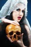Frau mit einem blassen Gesicht und einem Schädel. Lizenzfreies Stockbild