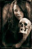 Frau mit einem blassen Gesicht und einem Schädel. Stockbild
