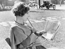 Frau mit einem Bleistift in ihrem Mund die Zeitung lesend (alle dargestellten Personen sind nicht längeres lebendes und kein Zust Stockfotografie