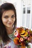 Frau mit einem Blumenstrauß der Blumen Stockfotografie