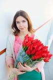 Frau mit einem Blumenstrauß der roten Tulpen lizenzfreie stockbilder