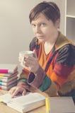 Frau mit einem Buch und einer Schale des heißen Getränks Lizenzfreies Stockbild