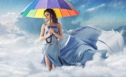 Frau mit einem bunten Regenschirm stockfotografie