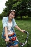 Frau mit einem Fahrrad draußen lächelnd Stockbild