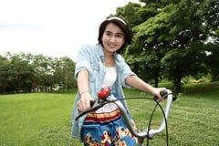 Frau mit einem Fahrrad draußen lächelnd Stockbilder