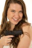 Frau mit einem falschen Lächeln der schwarzen Pistole Stockfotografie