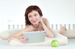 Frau mit einem grünen Apfel und Tablette am Bett lizenzfreies stockbild