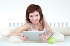 Frau mit einem grünen Apfel und Tablette am Bettlesungsebook lizenzfreie stockfotos