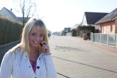 Frau mit einem Handy auf einer Dorfstraße Stockfoto