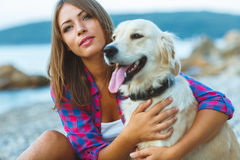 Frau mit einem Hund auf einem Weg auf dem Strand Stockfotografie