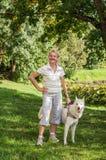 Frau mit einem Hund auf einem Weg im Park Lizenzfreies Stockbild