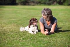 Frau mit einem Hund, der auf dem Gebiet liegt Stockbild