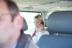 Frau mit einem Intelligenttelefon auf einem Rücksitze eines Autos Stockbilder