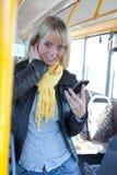 Frau mit einem Intelligenttelefon innerhalb eines Busses Stockbilder