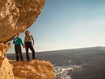 Frau mit einem Jungen, der auf einem Felsen steht Lizenzfreie Stockfotografie
