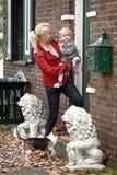 Frau mit einem Kind betreten ein Haus Lizenzfreies Stockbild