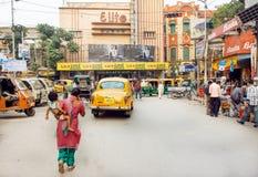 Frau mit einem Kind, welches die alte indische Straße mit Kinotheater und -hotels kreuzt Lizenzfreie Stockfotos