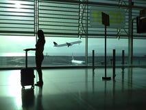 Frau mit einem Koffer, der in den Flughafen wartet Stockbilder