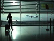 Frau mit einem Koffer im Flughafen Lizenzfreies Stockfoto