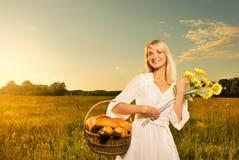 Frau mit einem Korb des Brotes Stockfotos
