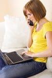 Frau mit einem Laptop auf einem Aufenthaltsraum stockfotografie