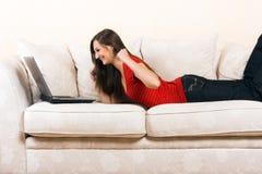 Frau mit einem Laptop auf einem Aufenthaltsraum stockbilder