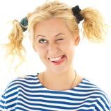 Frau mit einem lustigen Blick auf ihrem Gesicht lächelt Stockfotografie