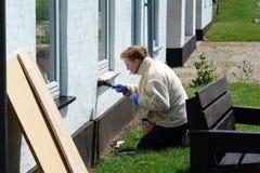 Frau mit einem Malerpinsel, der ein Haus malt Lizenzfreie Stockfotografie