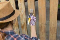 Frau mit einem Malerpinsel, der hölzerne Terrassengeländer malt Nebelige Fallinsel lizenzfreie stockfotografie