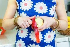 Frau mit einem Messer zieht einem Apfel ab Stockfotos