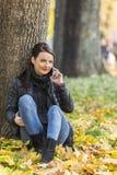 Frau mit einem Mobile in einem Wald im Herbst stockfotos