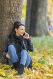 Frau mit einem Mobile in einem Wald im Herbst stockbild