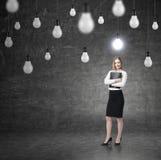 Frau mit einem Ordner und vielen Glühlampen Stockbilder