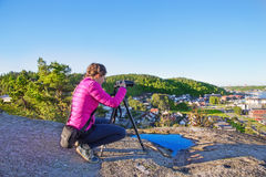 Frau mit einem photocamera früh morgens auf einem Berg im Sand Stockbild
