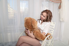 Frau mit einem Plüschbären, der auf einem Stuhl nahe dem Fenster sitzt Stockfoto