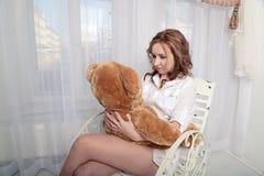 Frau mit einem Plüschbären, der auf einem Stuhl nahe dem Fenster sitzt Lizenzfreie Stockfotos