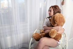 Frau mit einem Plüschbären, der auf einem Stuhl nahe dem Fenster sitzt Stockfotografie