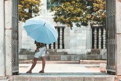 Frau mit einem Regenschirm vor einem Tempel in Vietnam stockfotografie