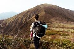 Frau mit einem Rucksack in den Bergen ist eine hintere Ansicht lizenzfreie stockfotografie