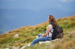 Frau mit einem Rucksack, der auf einem Felsen sitzt Lizenzfreie Stockbilder